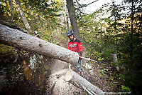 Lead mountain bike trail builder Aaron Rogers removes a tree from a trail with a chainsaw in Copper Harbor Michigan Michigan's Upper Peninsula.