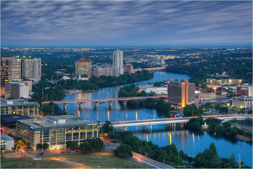 From high atop the Austin Skyline, this view looks southeast down Ladybird lake, across the 1st Stree Bridge and Congress Bridge, and onto the I-35 Bridge that spans the water. Also in view are the Austin Hyatt on the south side of Congress Avenue. Further down, the tallest building is the Milago Condominiums. This Austin Skyline image was captured from the 42nd floor of the Springs, Condominiums. The long exposure allowed the clouds to slide across the sky, giving motion to their movements.