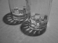 Glasses on a restaurant table refract light and shadow