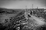 Widespread pollution in China is not always from industrial sources as demonstrated beside this dry river bed.  Woman returns to her neighborhood along a levee strewn with garbage in the late afternoon in Wuhai, Inner Mongolia, China.