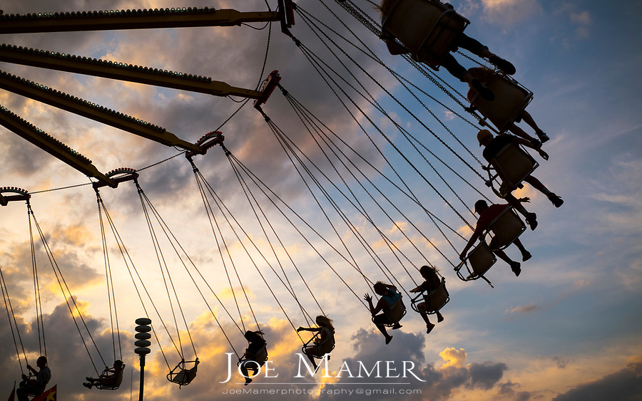 An amusement ride at a county fair sends riders soaring through the air at sunset.