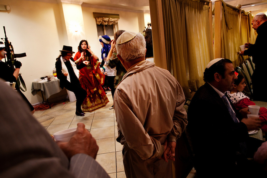 Los Angeles, California, March 19, 2011 - Though it is against custom, several male members of the Chabad Persian Youth Center watched the women dance during a celebration for Purim...Purim is a Jewish holiday that commemorates the deliverance of the Jewish people living in the Persian Empire from genocide at the hands of the political advisor, Haman, to the Persian King Ahasuerus, as documented in the Talmud's Book of Esther. It is celebrated by the reading of the Scroll of Esther or the Megillah, sending food gifts to friends, giving charity to the poor and celebrating with a festive meal. During the reading of the Megillah, when Haman's name is mentioned (which happens 54 times) the congregation engages in loud roars and the use of rattles in an effort to blot out his name. Today children and some adults dress in costume and masquerade to celebrate Purim. The custom is believed to have originated during the 15th century by Italian Jews influenced by the Roman carnival. One idea for the costumes is that God disguised his presence behind many of the natural events that happened during Purim. .
