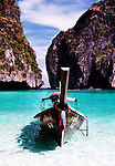 A passenger boat anchored near the beach at popular and beautifull Phi Phi island, Thailand.