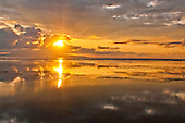 Rising sun, reflections and clouds at dawn seen in Sanur Beach in Bali, Indonesia