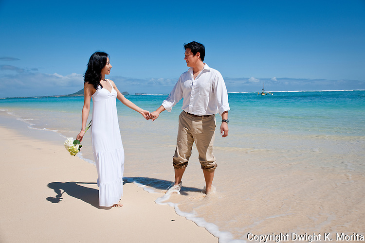 Asian bride and groom gaze at each other while holding hands on Lanikai beach. Couple celebrates their marriage with a honeymoon in Hawaii.