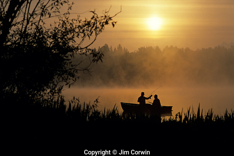 Sunrise at Lake Cassidy in fog with silhouetted fishermen in small rowboat getting ready to cast their lines, east of Marysville, Washington State USA.