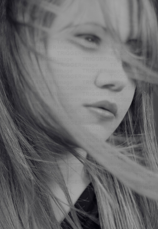 Black and white portrait of a beautiful teenager's face with her long hair blowing infront of her