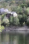 A log cabin on the cliff above a lake during the Fall season in Branson Missouri