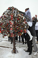 Moscow, Russia, 14/02/2011..A groom and wedding guests hoist a bride hanging a wedding padlock on an artificial tree in temperatures of minus 14C.