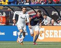 Vancouver Whitecaps FC substitute midfielder Pedro Morales (77) looks to pass as New England Revolution midfielder Andy Dorman (12) closes. In a Major League Soccer (MLS) match, the New England Revolution (blue/white) tied Vancouver Whitecaps FC (white), 0-0, at Gillette Stadium on March 22, 2014.