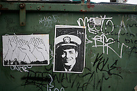 Graffiti and street art covers a dumpster in Bloomington, Indiana. Street art is a hidden part of the underground art and music culture of the city which is host to one of the United States hidden punk scenes.