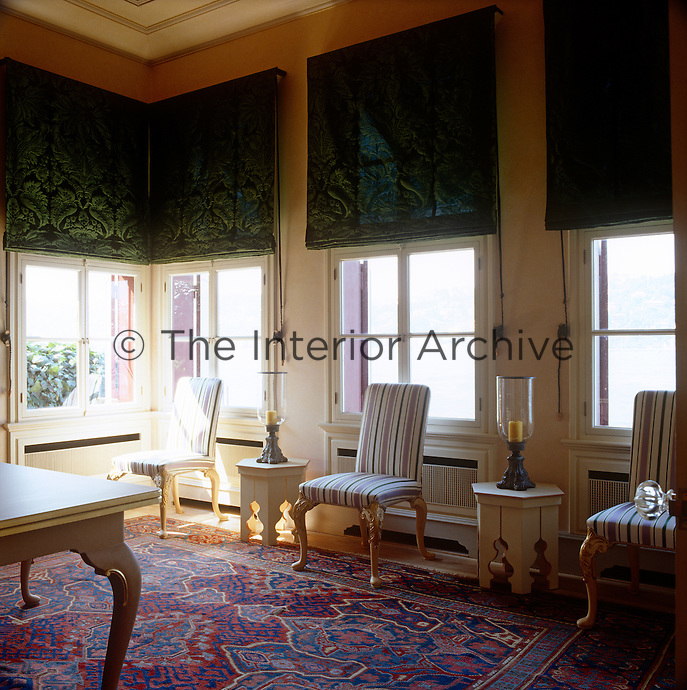 The dining room windows are dressed with green brocade blinds, while striped chairs line the edge of the room