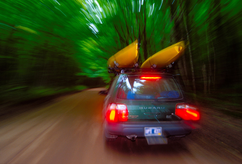 A CAR CARRYING SEA KAYAKS CRUISES  THE TREE COVERED H-58 IN THE PICTURED ROCKS NATIONAL LAKESHORE NEAR GRAND MARAIS, MICHIGAN.