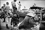 Buying breakfast from floating restaurant.  Vietnamese woman prepares breakfast for a customer from her sampan, Chong Kneas, Cambodia.