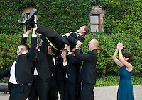 A groom is lifted into the air at the Culinary Institute in St. Helena after his Napa, CA.