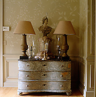 On a curvy antique chest in the dining room, French balustrade lamps flank a 1950s Adam-style stone bust