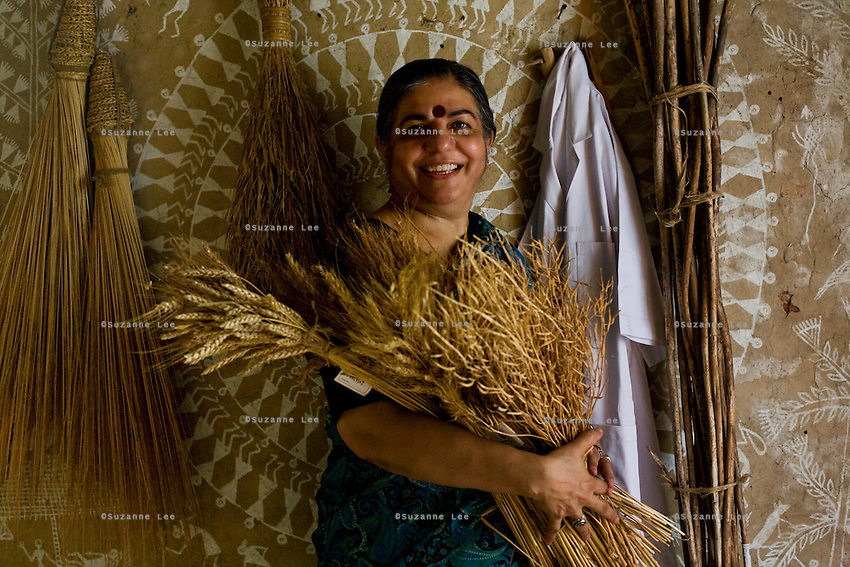 Dr. Vandana Shiva holds a bouquet of dried wheat, millet and fenugreek as she poses amongst hanging dried crops and her laboratory coat in the Navdanya Seed bank in Dehradun, Uttarakhand, India, on 6th September 2009. The inside walls of the seed bank have all been painted by Gujarati and Rajasthani tribal artists...Dr. Vandana Shiva, the founder of Navdanya Foundation and Bijavidyapeeth, is a physicist turned environmentalist who campaigns against genetically modified food and teaches farmers to rely on indigenous farming methods.. .Photo by Suzanne Lee
