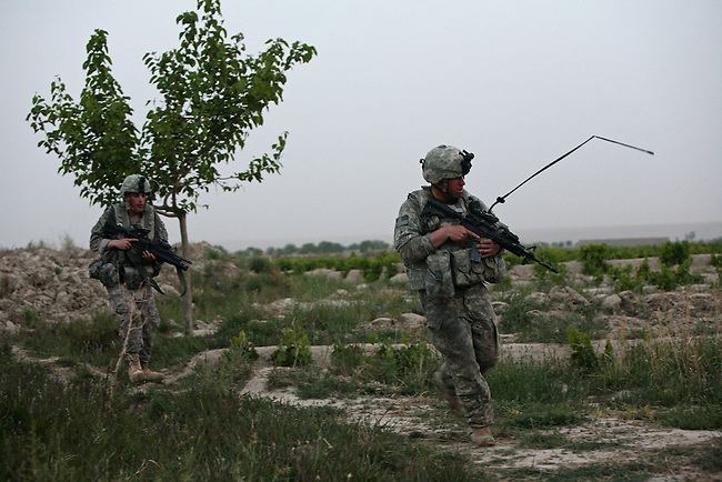 Soldiers from Company A, 2nd Battalion, 2nd Infantry Regiment run for cover after their patrol comes under Taliban fire near the village of Mira Hor in Kandahar province, Afghanistan. The fighters attacked with rifles and mortars, but no U.S. or Afghan troops were injured.  April 18, 2009. DREW BROWN/STARS AND STRIPES