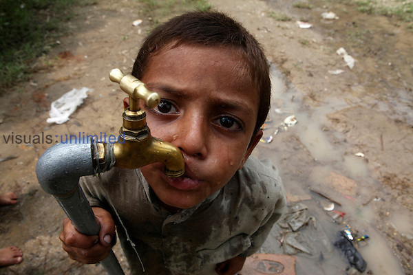 Boy drinking directly from a faucet provided as aid to victims of floods, Pakistan