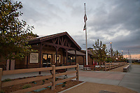 A 3/4 view of the front of the community and park staff building at Stanton Central Park at midnight.  Two tile photographs illustrate the front wall, along with two benches, a mock split rail fence, a flag post, and different colored concrete.  A cloudy sky makes up the background, with the remnants of the sunset reflected in the windows.