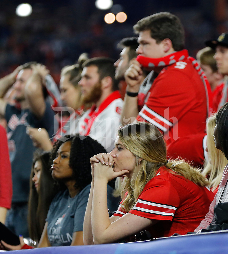 Ohio State Buckeyes fans show their dejection during the fourth quarter of the 31-0 loss to Clemson in the College Football Playoff semifinal Fiesta Bowl at University of Phoenix Stadium in Glendale, Arizona on Dec. 31, 2016. (Adam Cairns / The Columbus Dispatch)