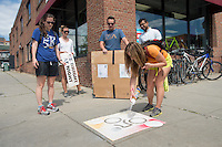 Class of 2017 students Bryce Bludevich, from left,  Amy Pennock  with Local Motion, Ryan Sofka, Syed Shehab and Erin Pichiotino spray paint graphics on Burlington sidewalks advising cyclists to use lighting while riding at night.,