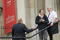 A photographer is escorted from the steps of the National Gallery, in London's Trafalgar Square