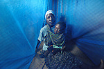 A mother cares for her son in a bed covered with an anti-malarial mosquito net, in Dundube Kadambo, Malawi.