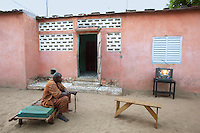 Senegal. Province of Thies. Village Thienaba Seck. A man seated on a bed watches television outside in the couryard of his house. 4.12.09 © 2009 Didier Ruef