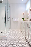 Honeycomb, a natural stone waterjet and hand cut mosaic shown in Thassos, Bardiglio and honed Calacatta, is shown here as a custom bathroom floor.<br />