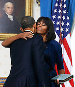 United States President Barack Obama (L) gets a hug from first lady Michelle Obama after he took the oath of office in the Blue Room of the White House in Washington, January 20, 2013. .Credit: Larry Downing / Pool via CNP