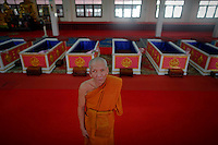 Thongchai, 59 year old Buddhist monk stand by coffins after he finished a ritual at Wat Prommanee temple in Nakhon Nayok province May 28, 2011. Hundreds of Buddhist believers pay small fee to lay in nine pink coffins at 9:09 am and 1:09 pm every day in Wat Prommanee temple during its unusual daily resurrection service that they believe will wash away bad luck and prolong life.      REUTERS/Damir Sagolj (THAILAND)