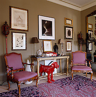 The red dog under the antique console table in the living room is a work by William Sweetlove and a photographic print by Hiroshi Sugimoto hangs on the wall above