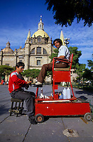 shoe polisher polishing the shoes of a man sitting in a tall red chair in front of the Guadaljara cathedral in Mexico
