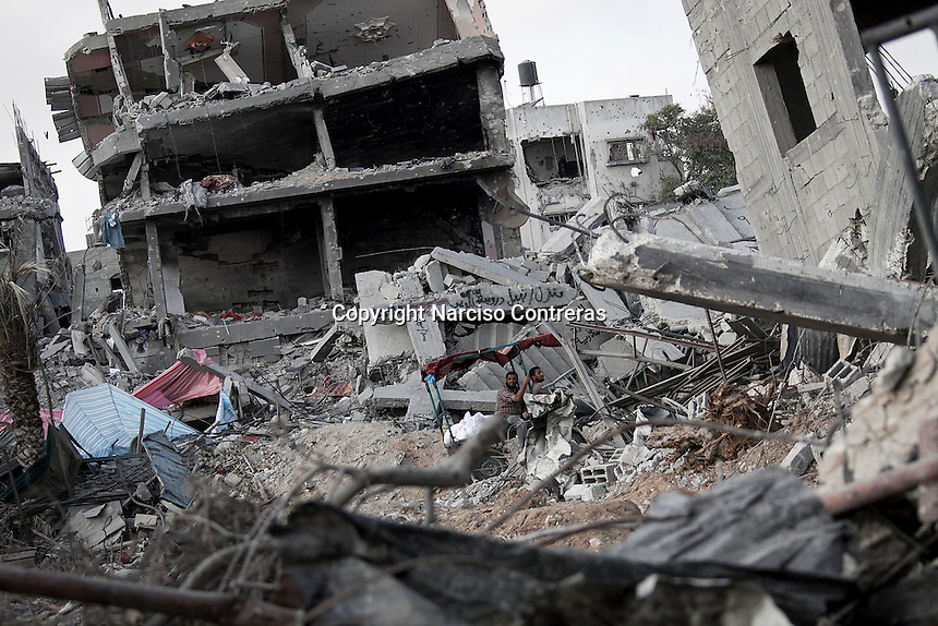 "In this Friday, Aug. 15, 2014 photo, Palestinian men ride by house buildings destroyed by israeli airstrikes and artillery shelling during the ""Protective Edge"" military operation in Shayaja neighborhood in Gaza City. After a five days truce was declared on 13th August between Hamas and Israel, civilian population went back to what remains from their houses and goods in Gaza Strip. (Photo/Narciso Contreras)"
