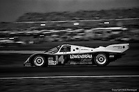 DAYTONA BEACH, FL: The Holbert Racing Porsche 962 103 of Al Unser, Jr., Derek Bell and Al Holbert is driven on the infield road course early in the evening during the 24 Hours of Daytona on February 3, 1985, at the Daytona International Speedway.