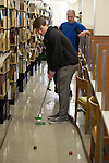 Zack Hadley putts a golf ball while father Keith Hadley watches during the Alden Open, a Dad's Weekend Mini-Golf event in Alden Library, on Saturday, November 7, 2015. Photo by Kaitlin Owens