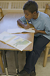 Oakland CA 2nd grade African American boy writing report on book he's just read in class