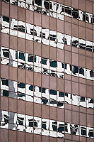 The windows of one office building wear the reflection of a neighboring building in downtown Oakland, Ca.