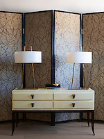 A custom-made parchment-covered cabinet in the living room is topped with a pair of 1950s table lamps, and the custom-made screen has panels covered in a Zoffany wallpaper.