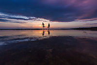A couple walking across tide pool rocks pause to take in the sunset at Shark's Cove, North Shore of O'ahu.