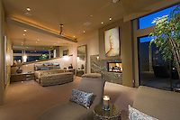 Dramatic modern master suite bedroom shown at night with fireplace and candles