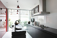 Worktops are made from chunky Black Zimbabwe granite and the splashback is a sheet of clear glass