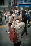 Tokyo, Japan - 22nd of July 2009 - A japanese woman taking a picture of the partial solar eclipse (75%) with her mobile phone.