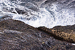 Waves crash along the shoreline against rocks.