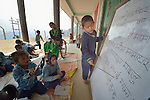 A boy reads aloud from a whiteboard in a class in Pida, a village in Nepal's Dhading District where the United Methodist Committee on Relief (UMCOR), a member of the ACT Alliance, is helping families to rebuild their lives in the wake of the 2015 earthquake that ravaged much of Nepal. UMCOR is constructing new classrooms to replace quake-damaged buildings, but in the meantime classes meet outside the old buildings.