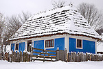 Ancient wooden country house with walls painted in blue and a thatched roof covered with snow in Ukraine Eastern Europe Winter scenic Horizontal orientation