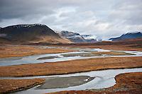 River flows through scenic mountain valley along Kungsleden trail, Lapland, Sweden