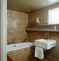 In this compact bathroom the space has been maximised by using recessed ceiling lights and painting the walls in a tone to match the terracotta tiles of the splashback