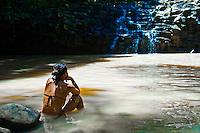 Teenage girl relaxing in waterfall pool at Twin Falls, Haiku, Maui